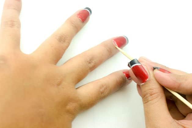Retier les ongles en gel avec un bâtonnet de manucure
